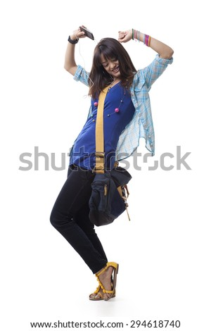 Full length of young college girl dancing while listening music over white background