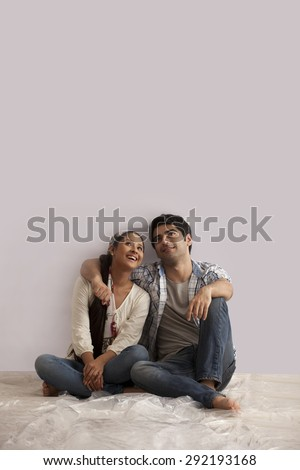 Full length of young couple looking up at copy space - stock photo