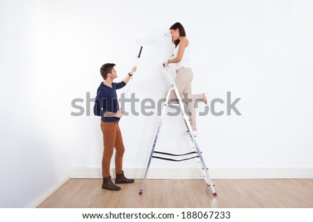 Full length of young couple painting new house