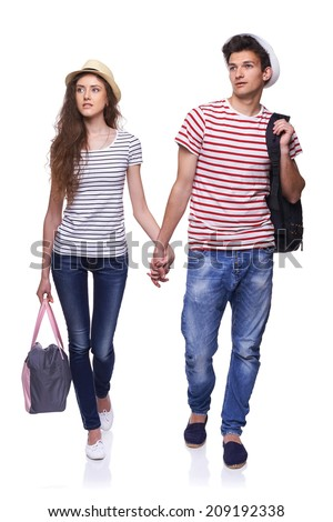 Full length of young couple walking with travel bags with joined hands looking way at copy space, isolated on white background - stock photo
