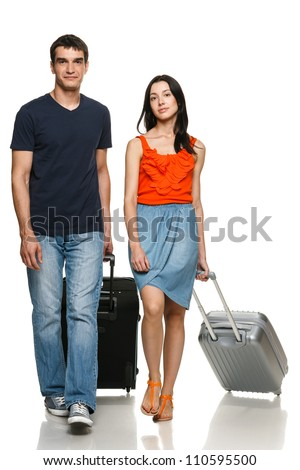 Full length of young couple walking with travel suitcases, over white background