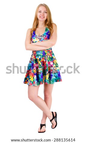Full length of young cute smile girl stands with crossed hands in mix color summer dress posing isolated on white background, positive human emotion, facial expression - stock photo