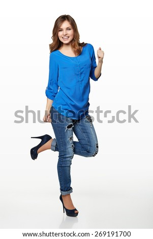 Full length of young cute smiling emotional girl giving you double thumbs up over white background