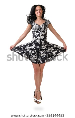 Full length of young elegant female in fashion dress, jumping over white background