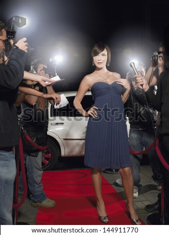 Full length of young female celebrity posing on red carpet surrounded by paparazzi - stock photo