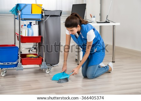 Full length of young female cleaner sweeping wooden floor in office - stock photo