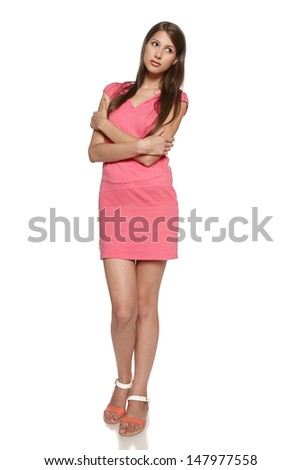 Full length of young female feeling uncomfortable embracing herself against a white background - stock photo