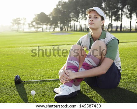 Full length of young female golfer with ball and club sitting on golf course - stock photo