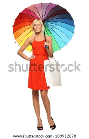 Full length of young female in bright red dress standing under rainbow umbrella and holding shopping bag, over white background