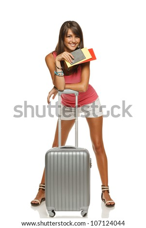 Full length of young female in casual leaning on the travel bag, holding passport and tickets, ready to leave for vacations, isolated on white background