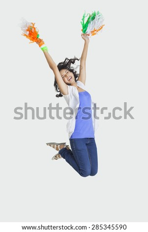 Full length of young female jumping in mid-air with Indian tricolor pom poms over white background - stock photo