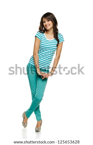 Full length of young flirty female in turquoise pants and t-shirt, over white background - stock photo