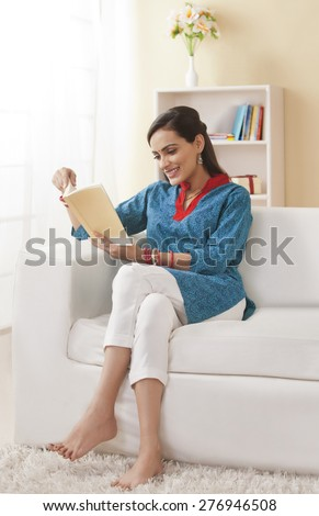 Full length of young Indian woman reading book on sofa - stock photo