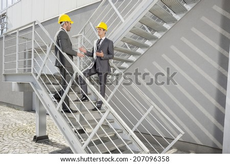 Full length of young male architects discussing on steps - stock photo