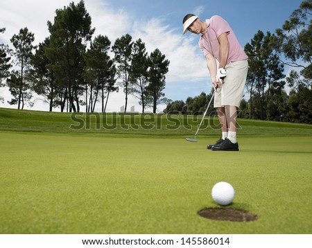 Full length of young male golfer playing golf - stock photo