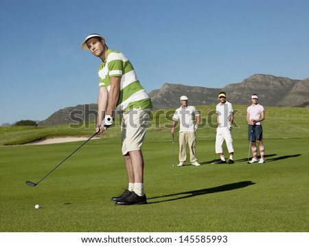 Full length of young male golfer playing golf with competitors in background