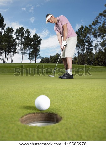 Full length of young male golfer putting ball on green - stock photo