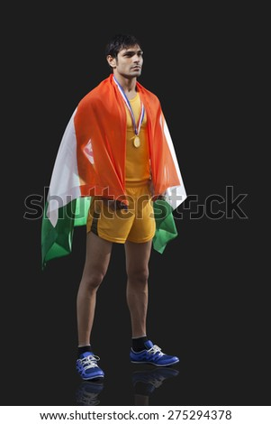 Full length of young male medalist with Indian flag looking away against black background - stock photo