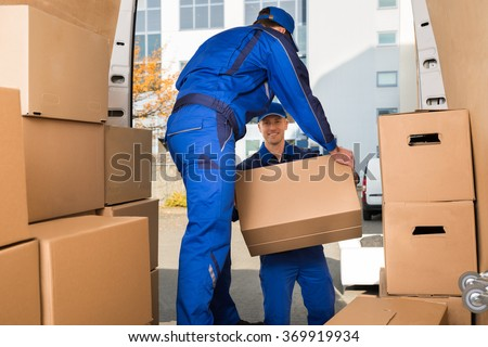 Full length of young male movers carrying sofa outside truck on street - stock photo