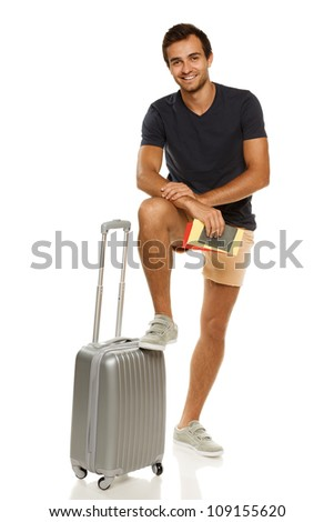 Full length of young male standing with silver suitcase, holding tickets and passport, with his leg on the suitcase, isolated on white background - stock photo