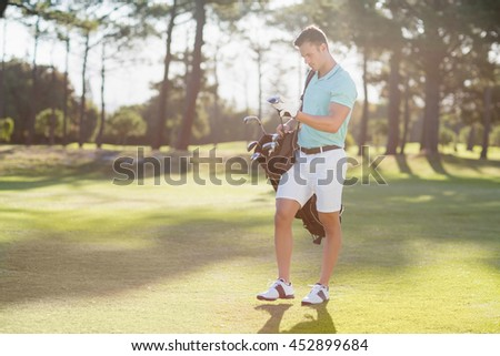 Full length of young man carrying golf bag while standing on field