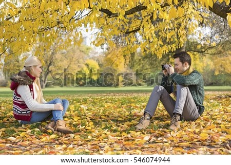 Full length of young man photographing woman in park during autumn