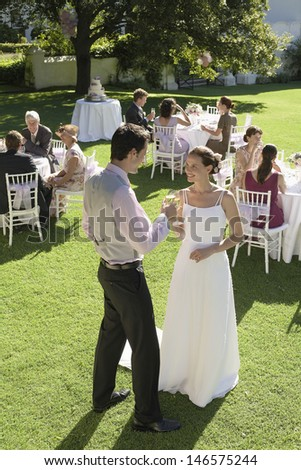 Full length of young newlywed couple toasting champagne while wedding guests sitting in garden - stock photo