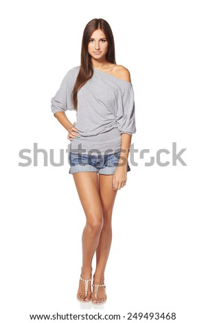 Full length of young slim tanned female in denim shorts standing with hand on hip, isolated on white background - stock photo