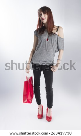Full Length of Young Trendy Teenage Woman Standing in Studio Holding Single Red Shopping Bag on White Background - stock photo