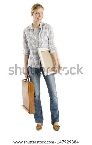 Full length of young woman carrying canvas and wooden case while looking away against white background
