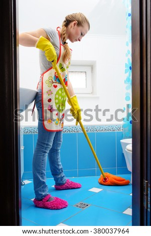 Full length of young woman cleaning ceramic floor of bathroom at home - stock photo