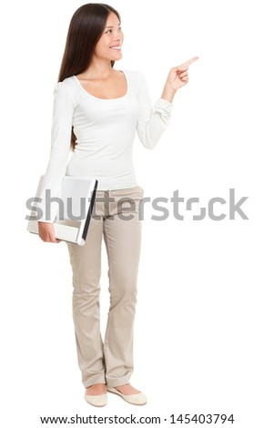 Full length of young woman holding laptop while pointing at copyspace isolated on white background - stock photo