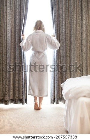Full length of young woman in bathrobe opening bedroom curtains at hotel room - stock photo