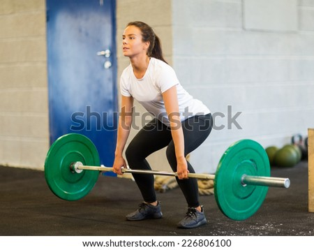 Full length of young woman lifting barbell in gym - stock photo