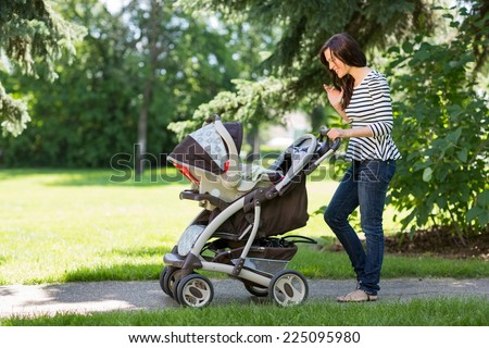Full length of young woman looking into baby carriage in park - stock photo