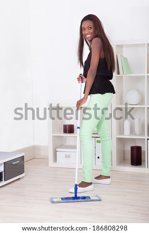 Full length of young woman mopping floor in living room - stock photo