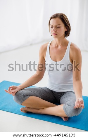 Full length of young woman performing yoga at fitness studio
