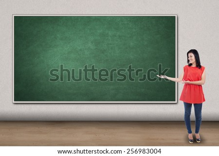 Full length of young woman showing empty blackboard for copyspace - stock photo