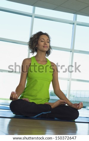 Full length of young woman sitting in lotus position at gym