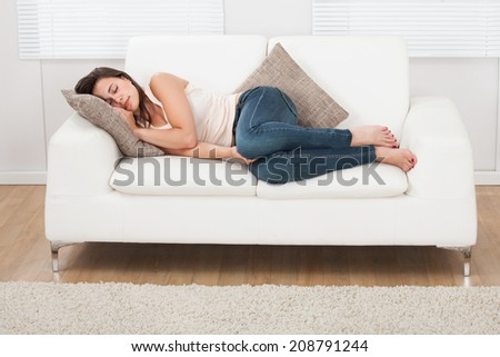Full length of young woman sleeping on sofa at home - stock photo