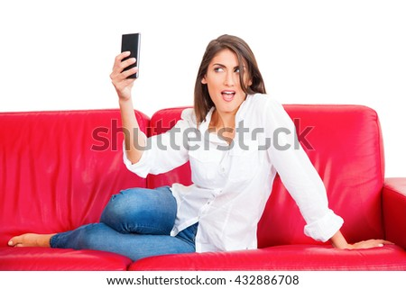 Full length of young woman taking selfie. Beautiful female is posing while holding smart phone. She is sitting on red sofa isolated on white background. - stock photo