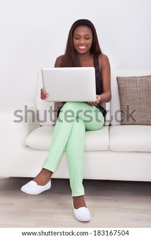 Full length of young woman using laptop while sitting on sofa in living room - stock photo
