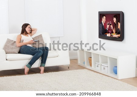 Full length of young woman watching television while lying on sofa at home - stock photo