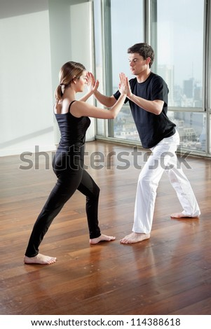 Full length of young yoga partners practicing yoga exercise at gym - stock photo
