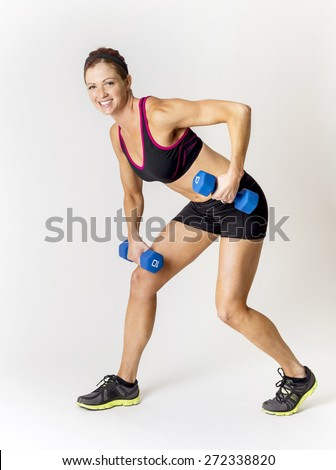 Full length photo of a beautiful, smiling fitness woman lifting weights during a workout. Indoor on a white background - stock photo
