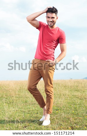 full length photo of a casual young man outdoor standing with a hand in his pocket and passing the other through his hair while smiling for the camera - stock photo