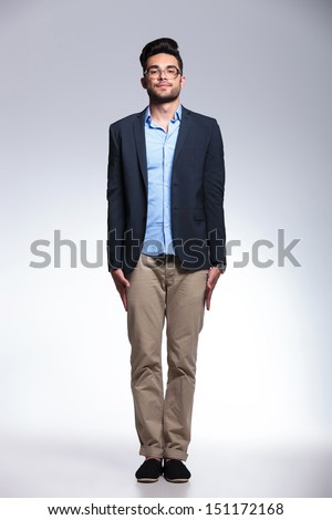 full length photo of a casual young man standing in attention with his palms along his body and looking at the camera. on gray background - stock photo