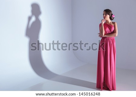 full length photo of a young beauty woman holding her hand at her chin and pensively looking at the camera. on a light gray background with shadow - stock photo