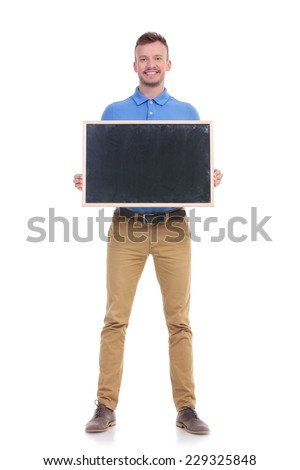 full length photo of a young casual man holding a blank blackboard with both hands and smiling for the camera. isolated on a white background - stock photo