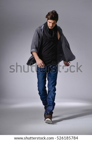 full length photo of a young casual man in jeans walking posing-light background